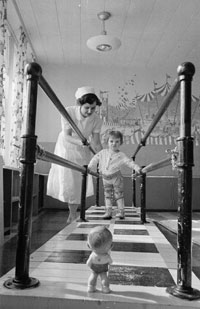 Mrs. E. Marr, physiotherapist, with Gifford, 2 1/2 yrs old, at the walking bars